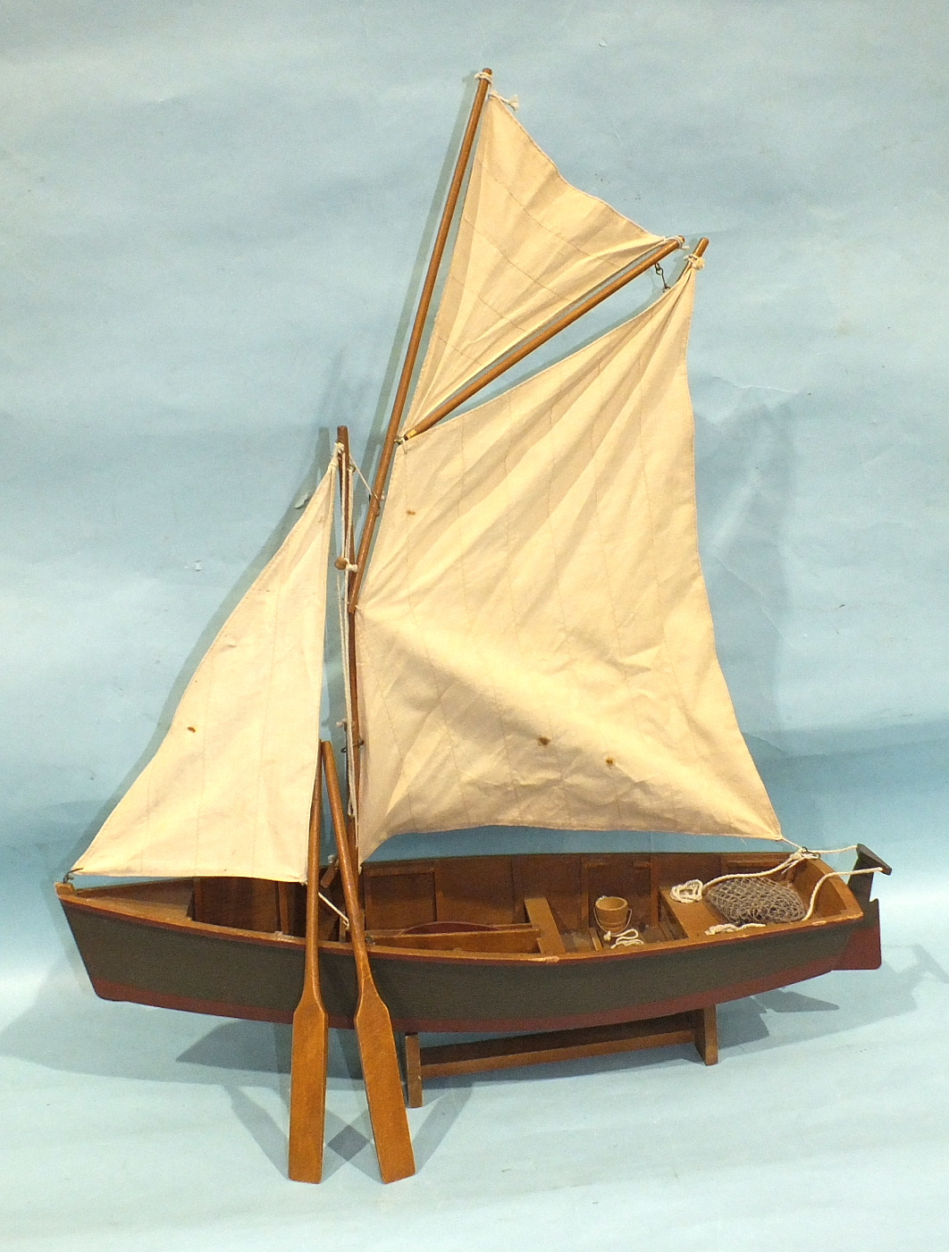 Lot 71 - A wooden model of a fishing smack, with gaff rig, crab pot, bucket, net and oars, on stand, 57cm