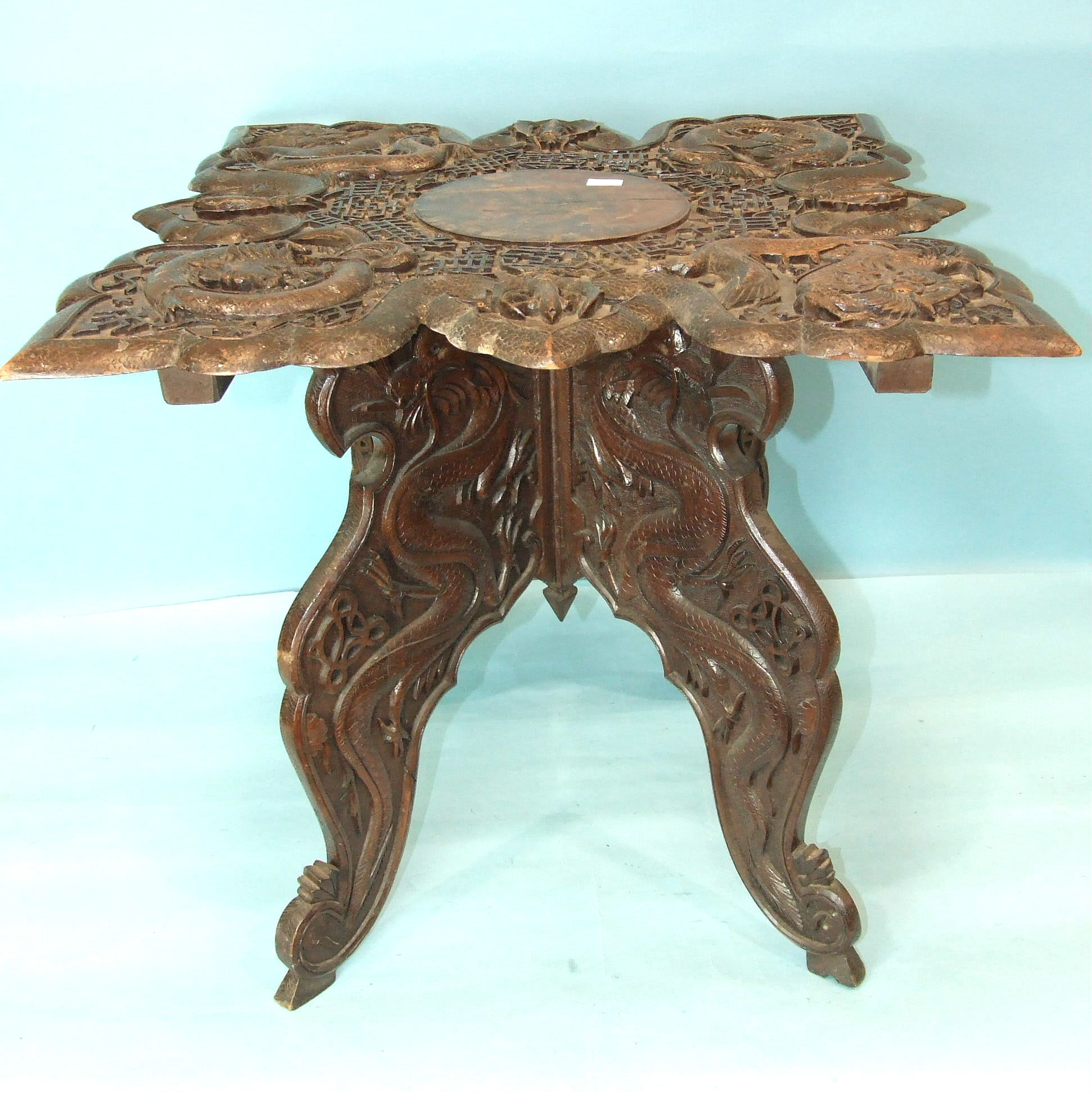A Chinese carved wood occasional table decorated overall with dragons and characters, 60cm square,