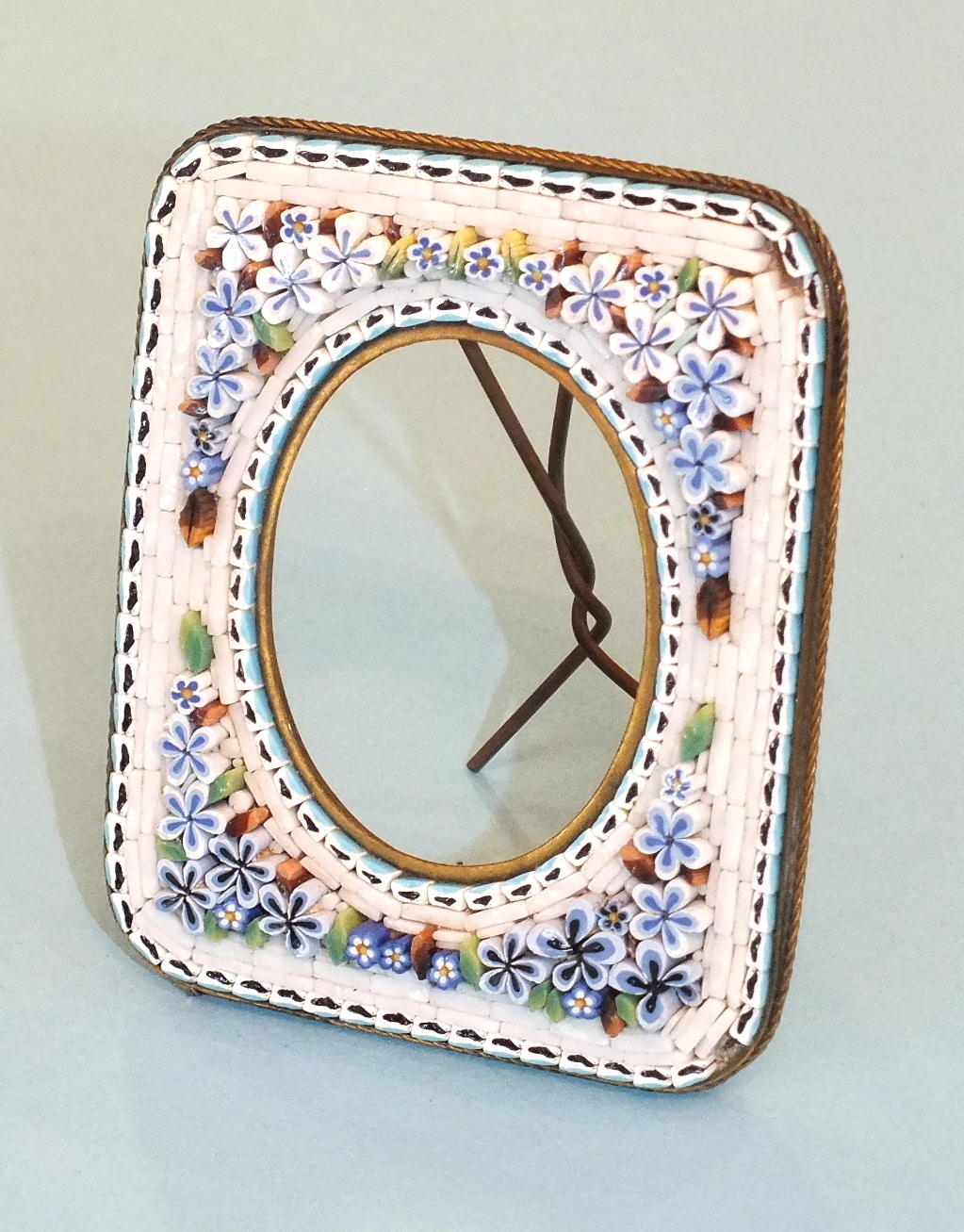 Lot 189 - A miniature glass mosaic picture frame decorated with blue and white flowers around an oval