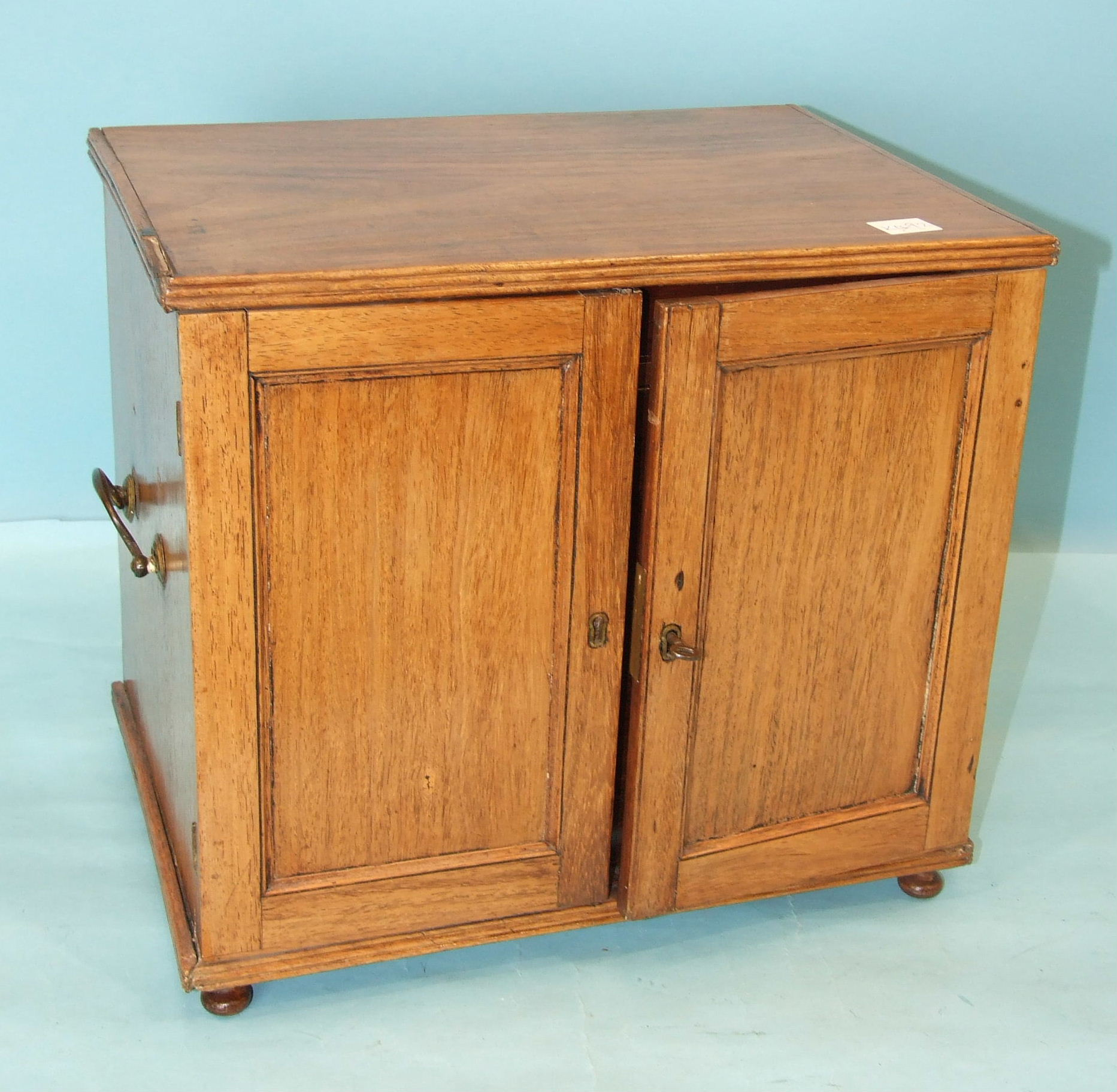 A 19th century hardwood collector's chest, having a pair of panelled doors enclosing six small