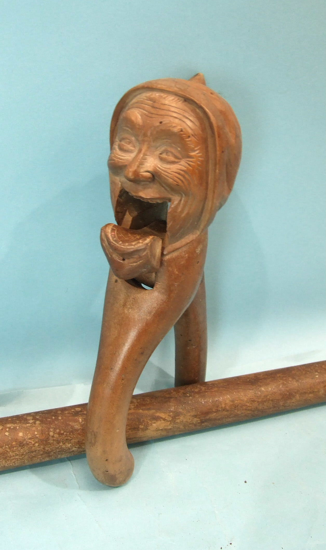 Lot 128 - A 19th century Continental carved wood nut cracker in the form of a woman wearing a night cap, a