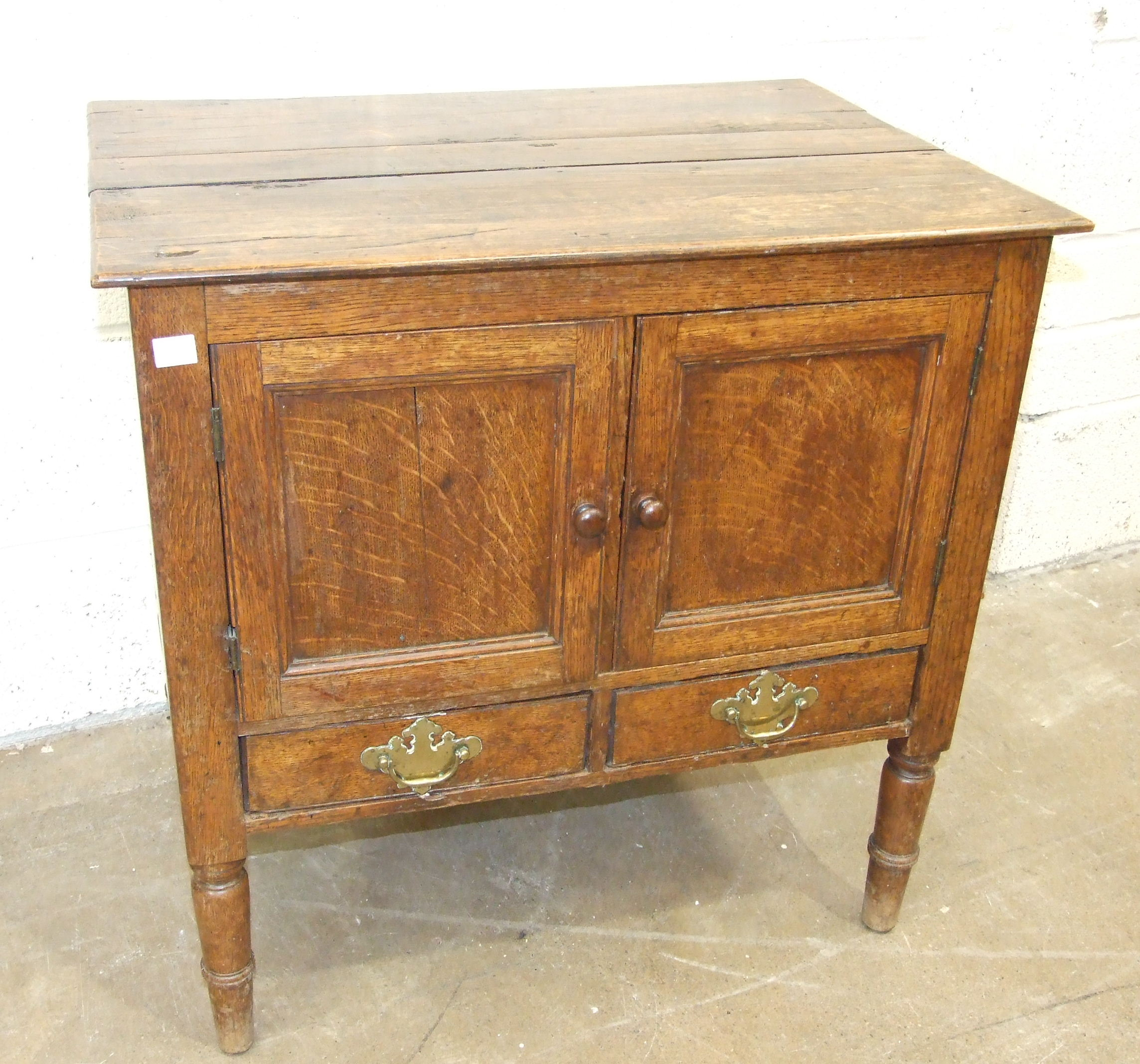 An antique oak pot cupboard having a pair of panelled doors and two small drawers, 70cm wide, 70cm