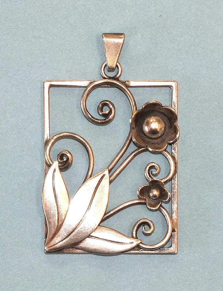 A Georg Jensen silver pendant of rectangular form, with applied flowers, tendrils and leaves, marked
