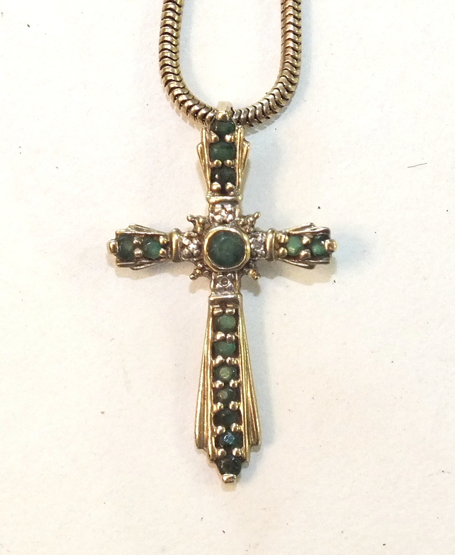 Lot 297 - A 9ct gold cross pendant set emeralds and diamond points, on 9ct gold snake-link chain, 7g.