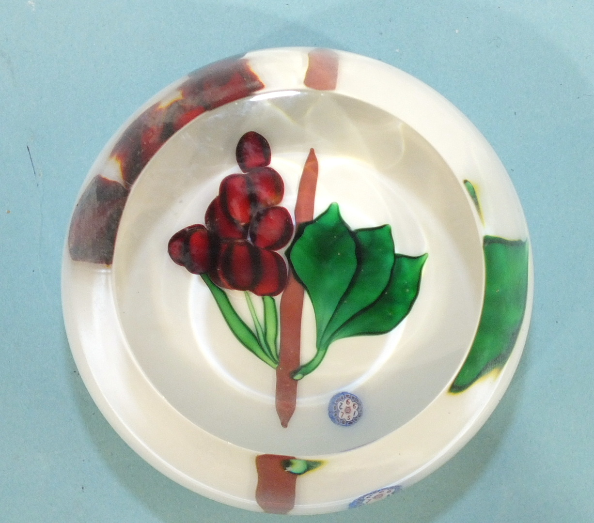 Lot 259 - A modern St Louis glass paperweight decorated with berries and leaves, 7cm diameter, 4cm high, dated