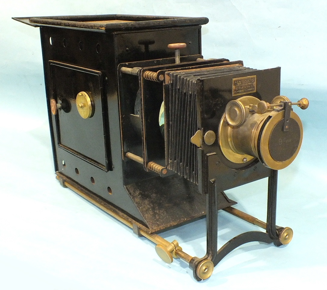 A Newton & Co. magic lantern with adjustable 9'' focus lens, bellows and Japanned tin body, in metal