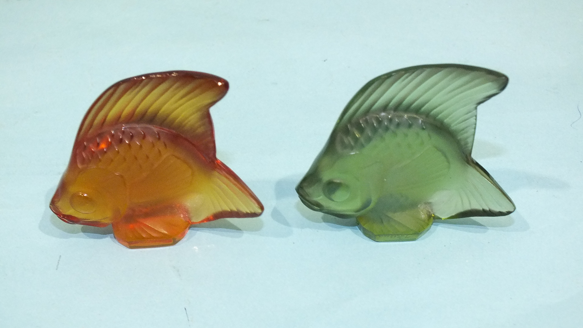 Lot 255 - A modern Lalique frosted green glass model of an angel fish and a similar amber glass fish, both