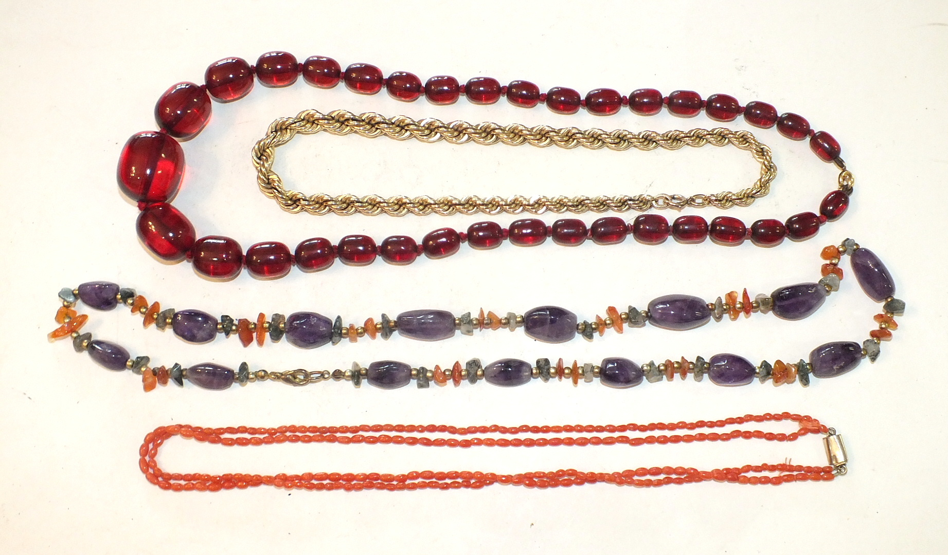Lot 294 - A string of graduated Bakelite 'cherry amber' beads, a coral bead necklace and two other