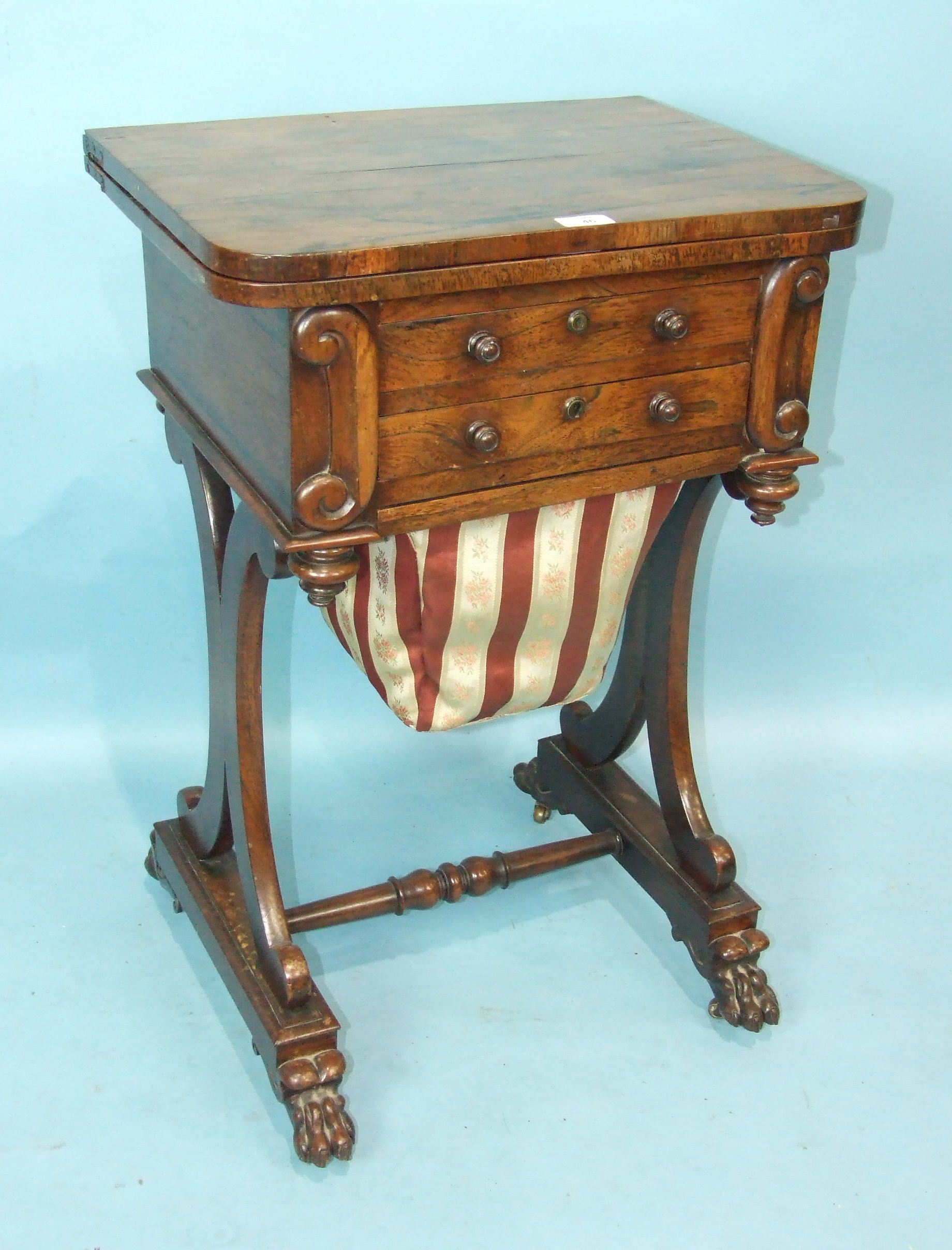 An early-19th century rosewood games and work table, the folding swivel top with satinwood and ebony