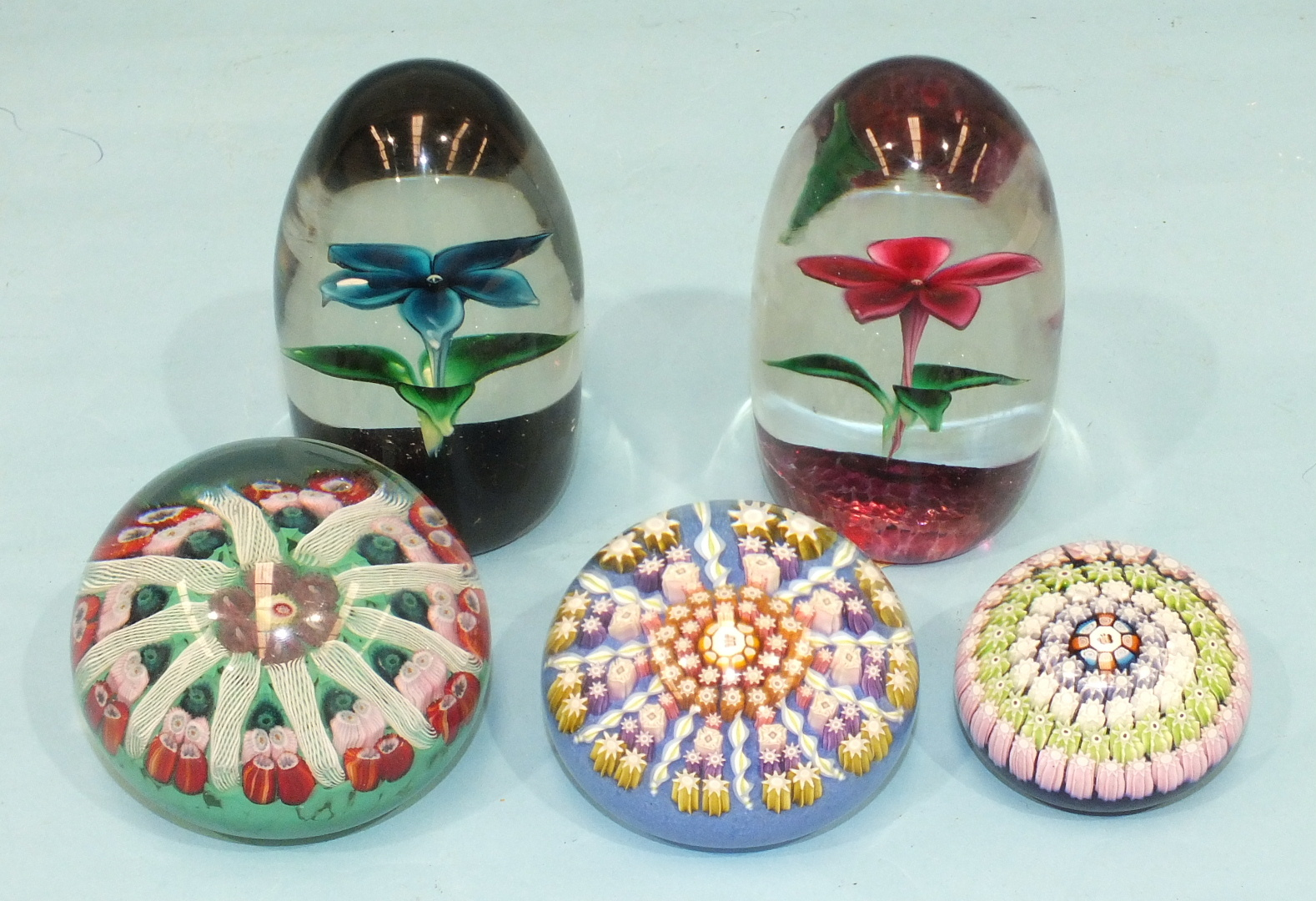 Lot 251 - Two Perthshire millefiore glass paperweights and three Strathearn glass paperweights, (5).