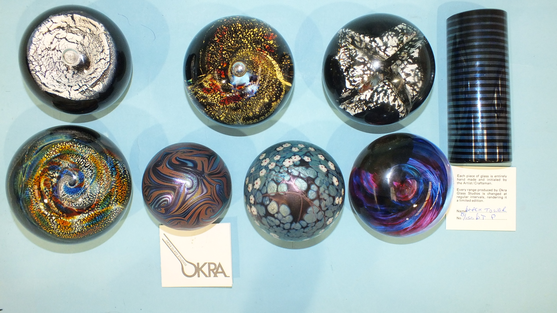 Lot 250 - Three Okra Glass Studios paperweights, 'Black Tower' 13/150, 'Nebular' No.15 and one other floral