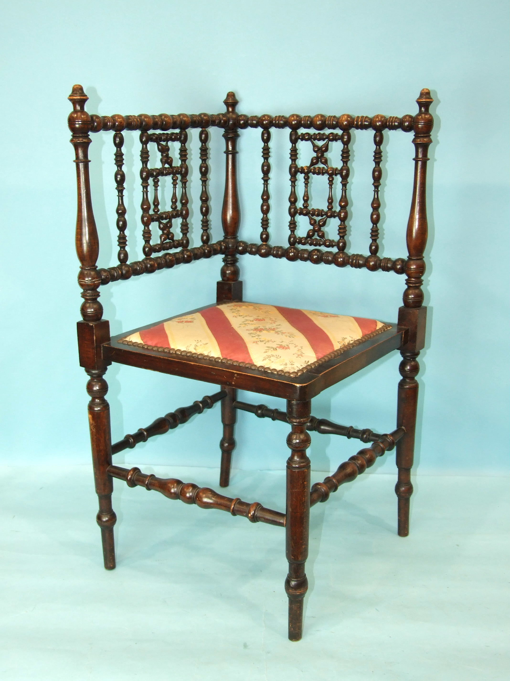 A stained wood bobbin-turned corner chair with padded seat, 76cm high.
