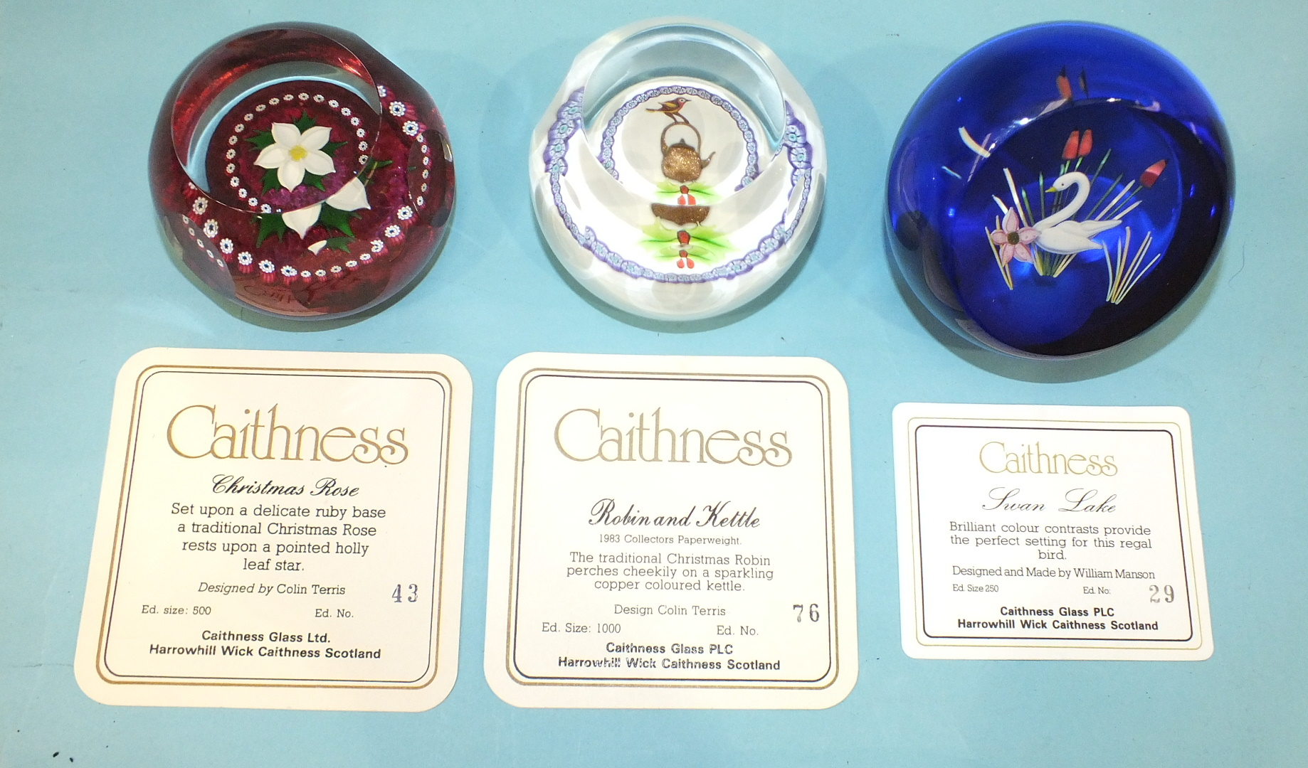 Lot 243 - Three limited-edition Caithness glass paperweights, 'Robin and kettle' 76/1000, 'Christmas Rose'
