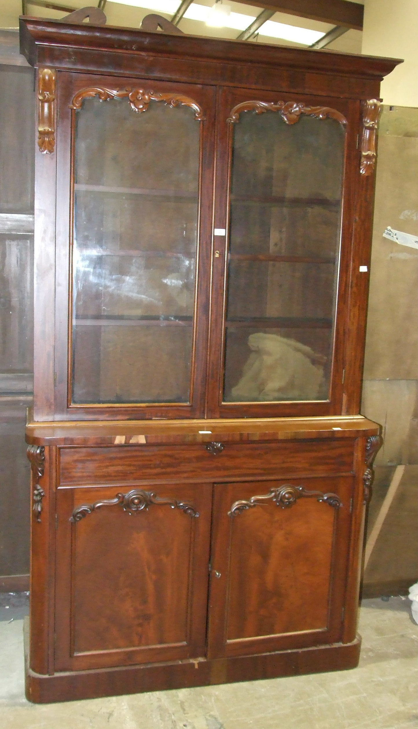 A Victorian mahogany bookcase, the cornice above a pair of glazed doors, a drawer and cupboard