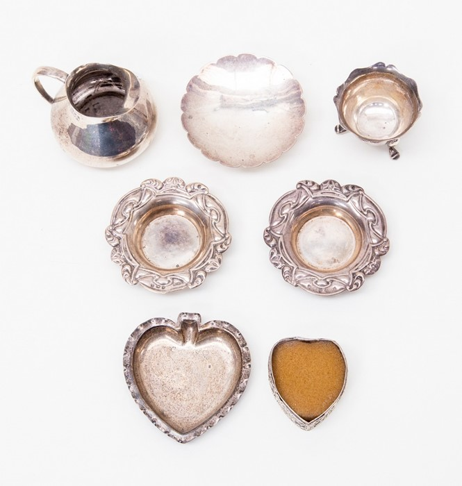 Lot 52 - A squat silver cream jug, London 1915, a pair of silver pin dishes Birmingham 1907, two other silver