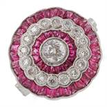 RUBY AND DIAMOND TARGET RING, set with a central old cut diamond, calibre cut rubies and round cut