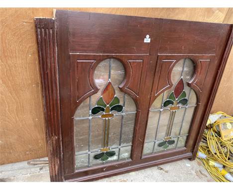 A WOODEN FRAMED WINDOW WITH STAINED GLASS
