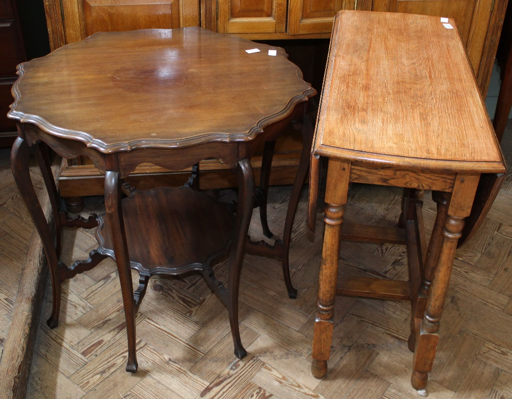 Lot 1037 - An mahogany reproduction shaped top occasional table with under tier and oak drop leaf table