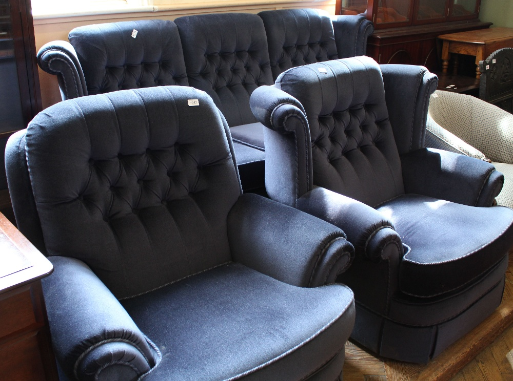 Lot 1032 - A blue velour button back three piece suite comprising a three seater sofa and two armchairs