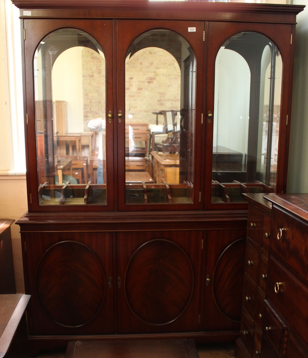 Lot 1034 - A large solid glazed top cabinet with three cupboards below