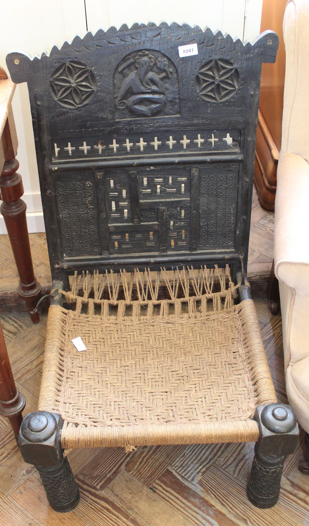Lot 1036 - An Indian carved chair with woven seat and back inlaid with Hindu God Ganesh