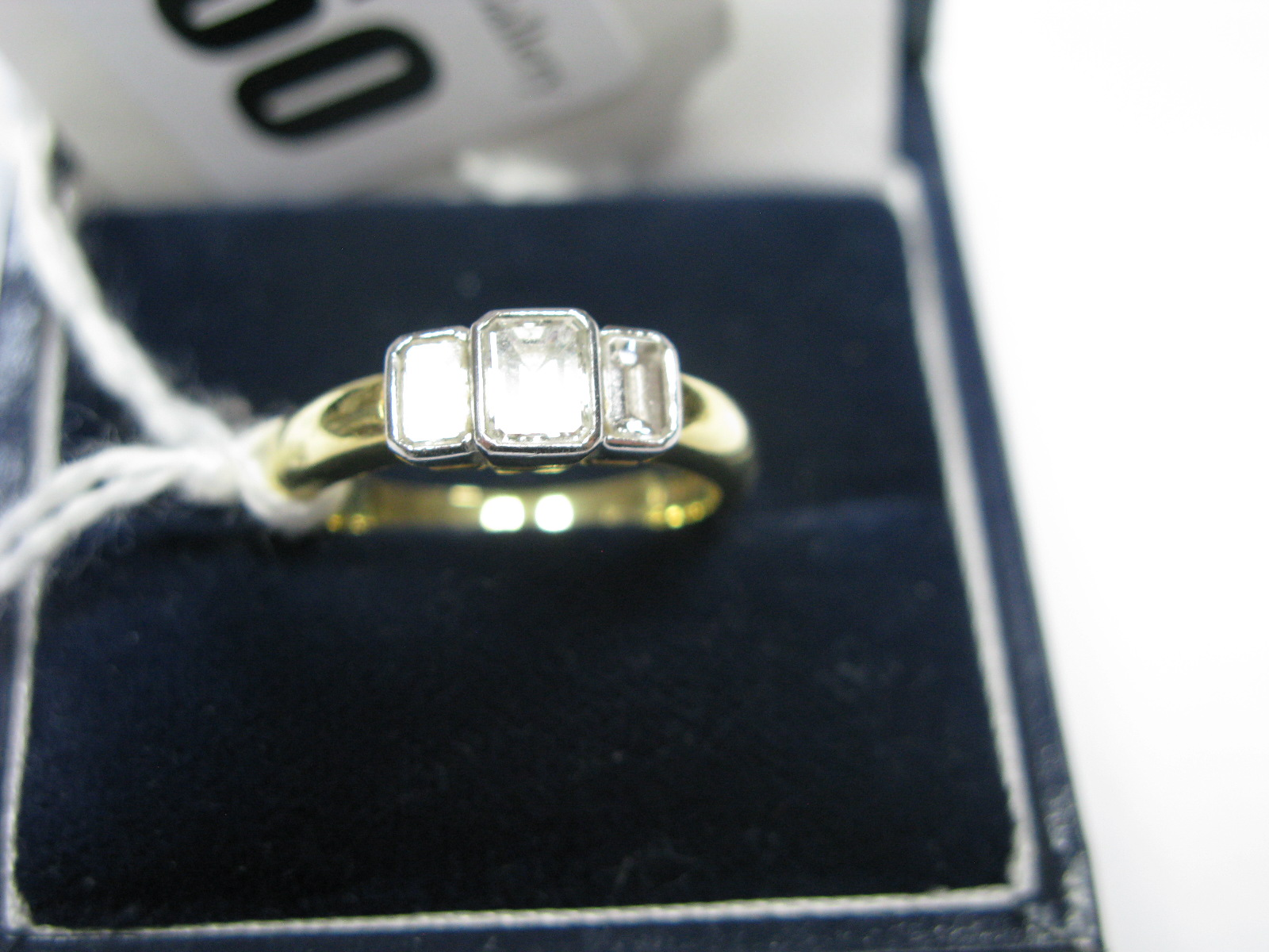 Lot 1350 - A Modern 18ct Gold Three Stone Diamond Ring, collet rubover set with three rectangular cut stones,