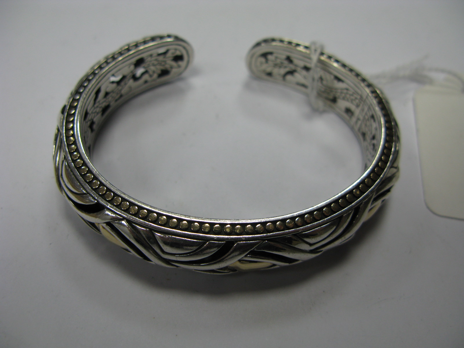 "Lot 1372 - A Modern Bangle, of pierced design, with gold coloured relief, stamped ""925 1/3 18K"", with dragon"