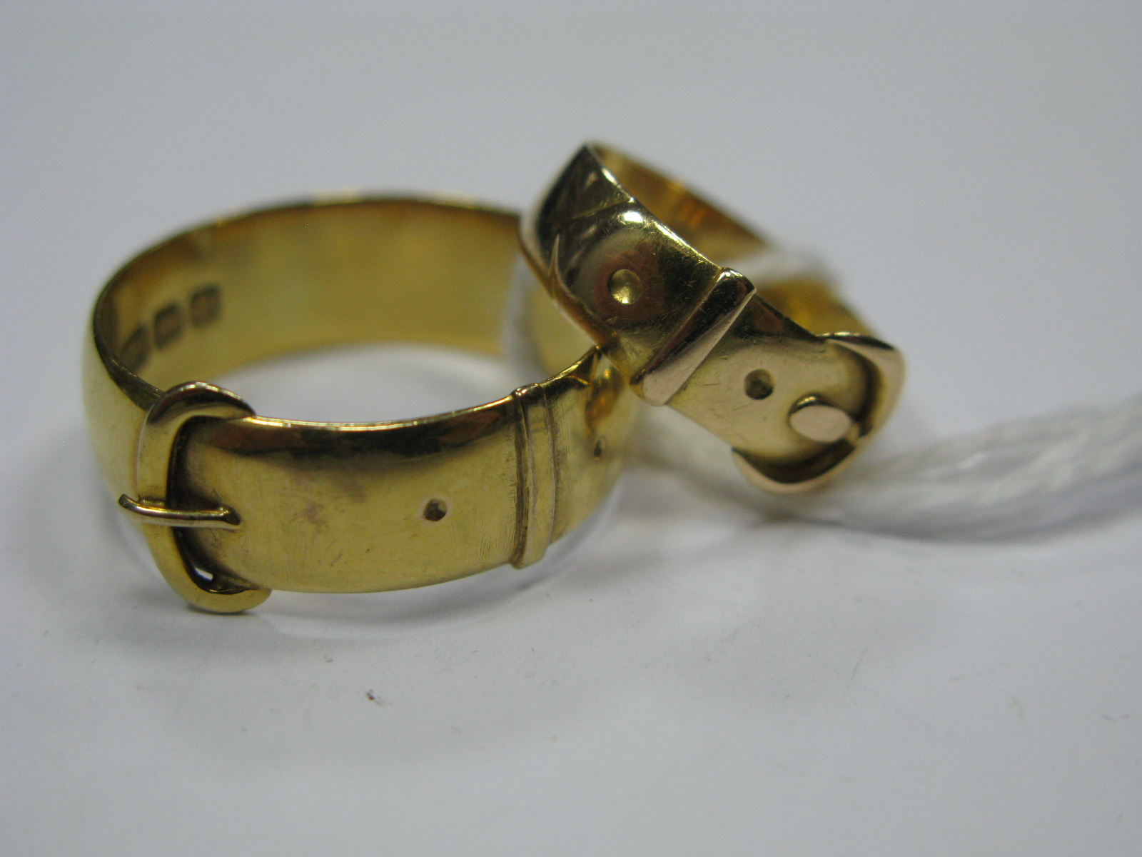 Lot 1348 - A 9ct Gold Gent's Buckle Ring; together with another buckle ring (hallmark worn). (2)