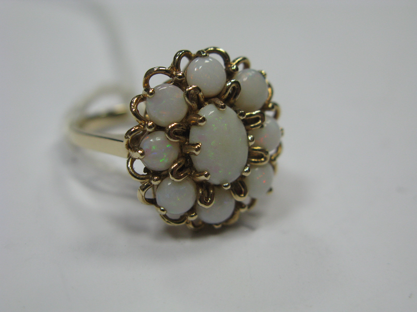 Lot 1358 - A 9ct Gold Opal Set Cluster Ring, of openwork design.