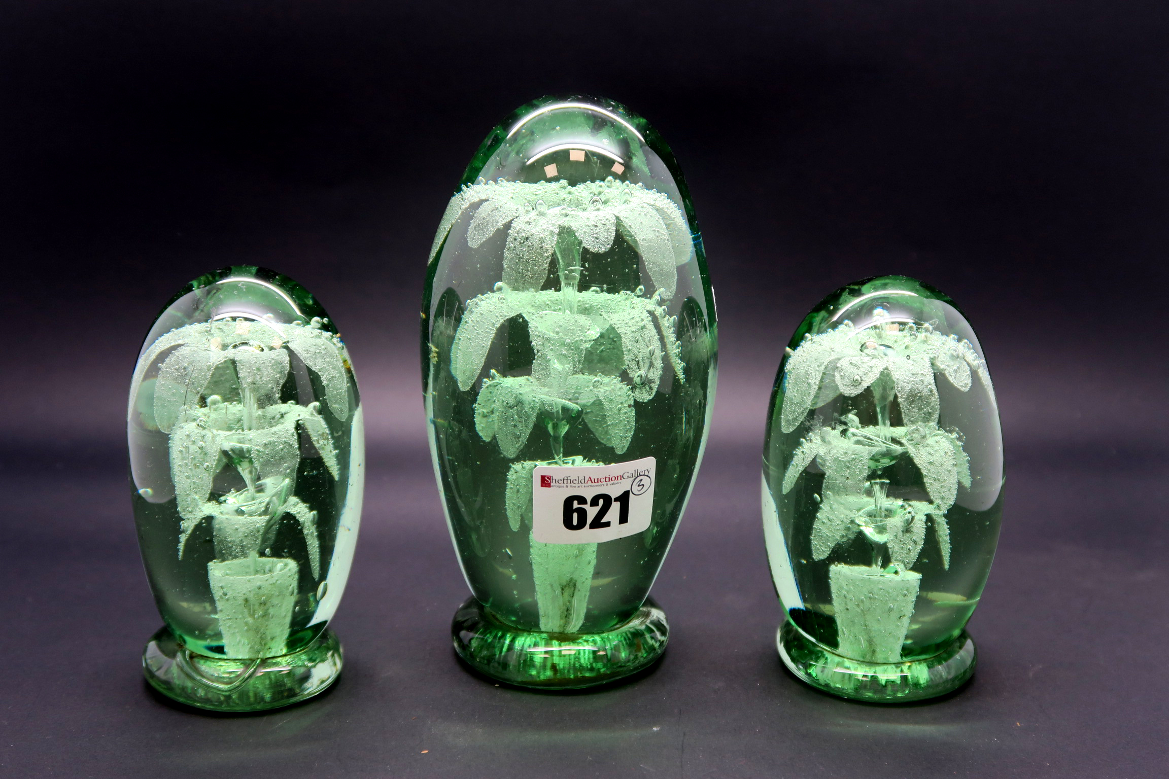 Lot 621 - A Garniture of Three Late XIX Century Green Glass Dumps, with flower head insets, 11cm and 15cm