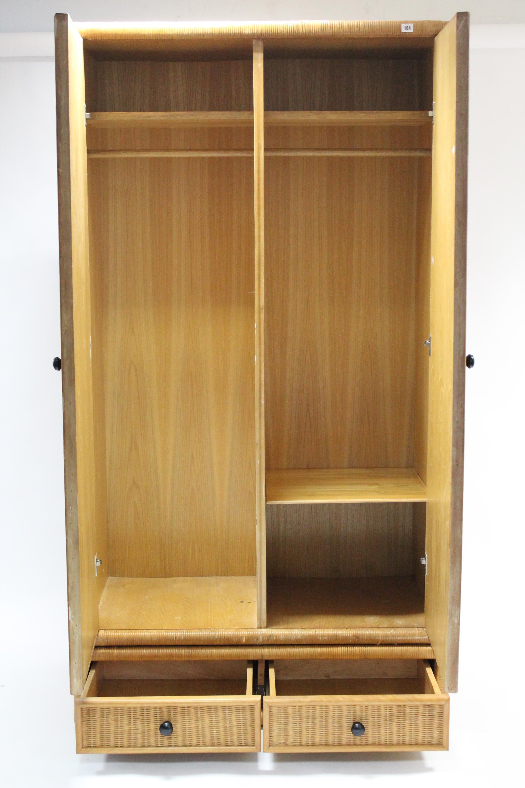 "Lot 184 - A rattan-covered twin-door wardrobe, 43¼"" wide x 69½"" high."