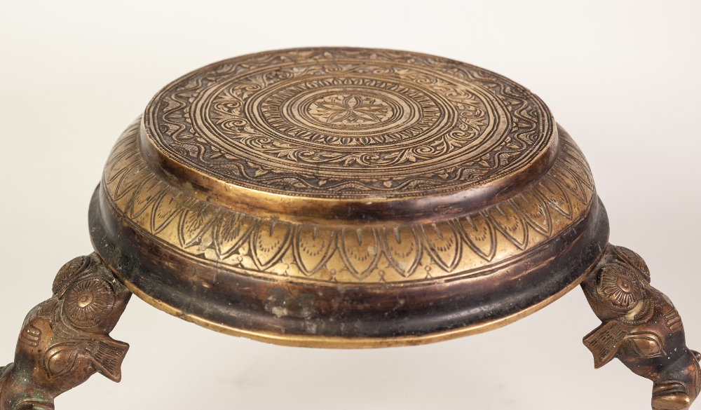Lot 80 - INDIAN CAST AND ENGRAVED BRASS THREE LEGGED STAND, the circular top profusely decorated with bands