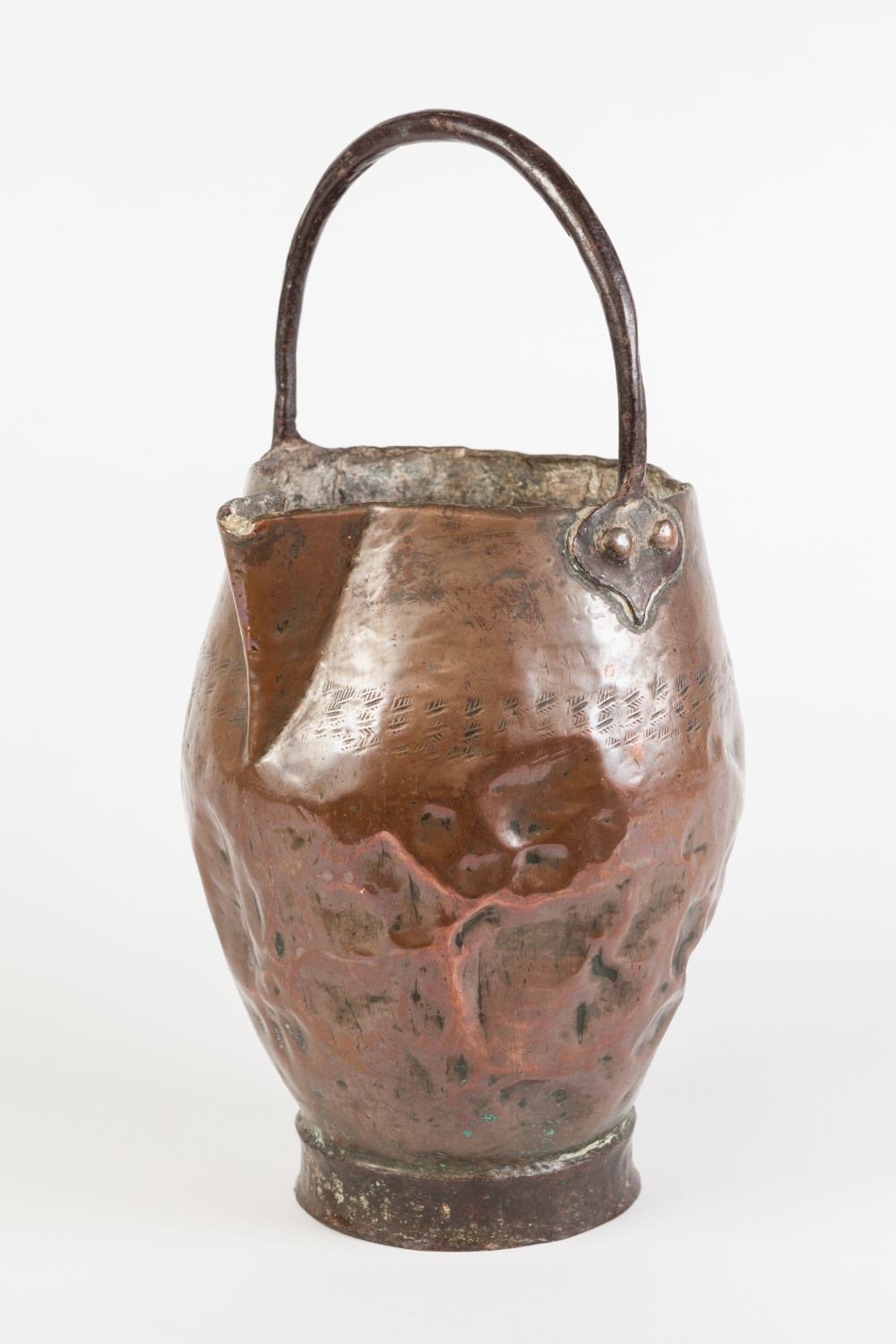 Lot 79 - AN ANTIQUE COPPER JUG, bellied form with pinched spout, hammered band marking, riveted overhead