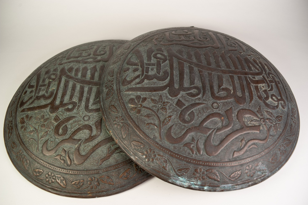 Lot 93 - PAIR OF MIDDLE EASTERN EMBOSSED COPPER ALLOY WALL HANGINGS, each of domed, circular form, the centre