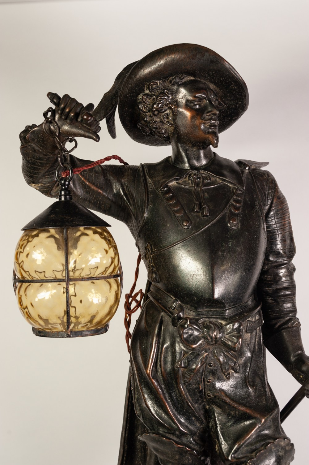 Lot 107 - VICTORIAN PATINATED SPELTER 'DON CESAR' MUSKETEER PATTERN FLOOR LAMP, modelled standing with sword