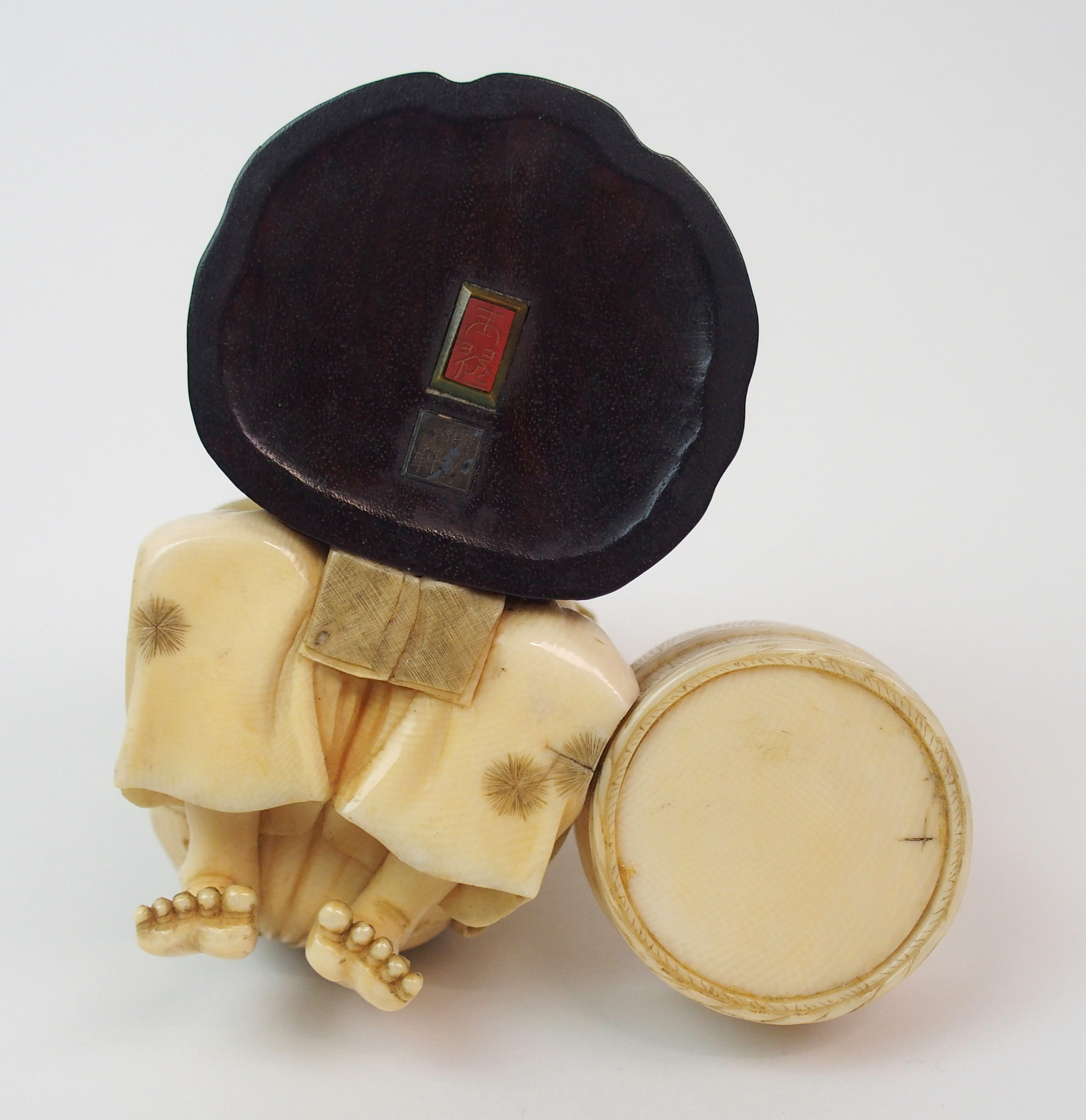 Lot 24 - AN IVORY, WOOD AND METAL OKIMONO OF A MIRROR MAKER kneeling and polishing a mirror on a tree