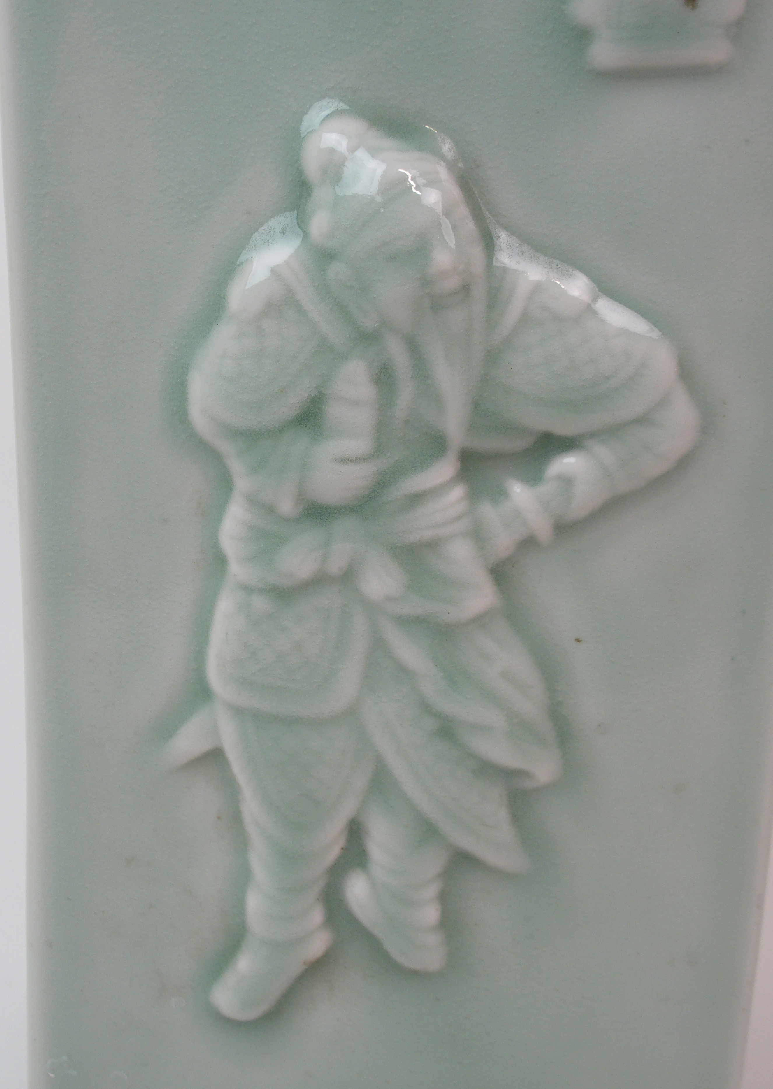 Lot 7 - A CHINESE CELADON CONG VASE moulded with figures and symbols with foliate neck and ring foot,