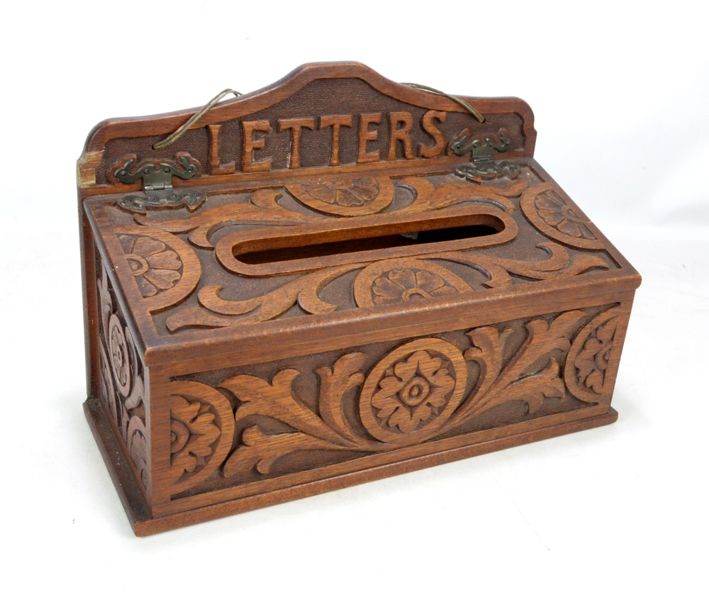 Lot 57 - A late Victorian carved oak wall mounted letter box, the shaped back rail inscribed 'Letters',