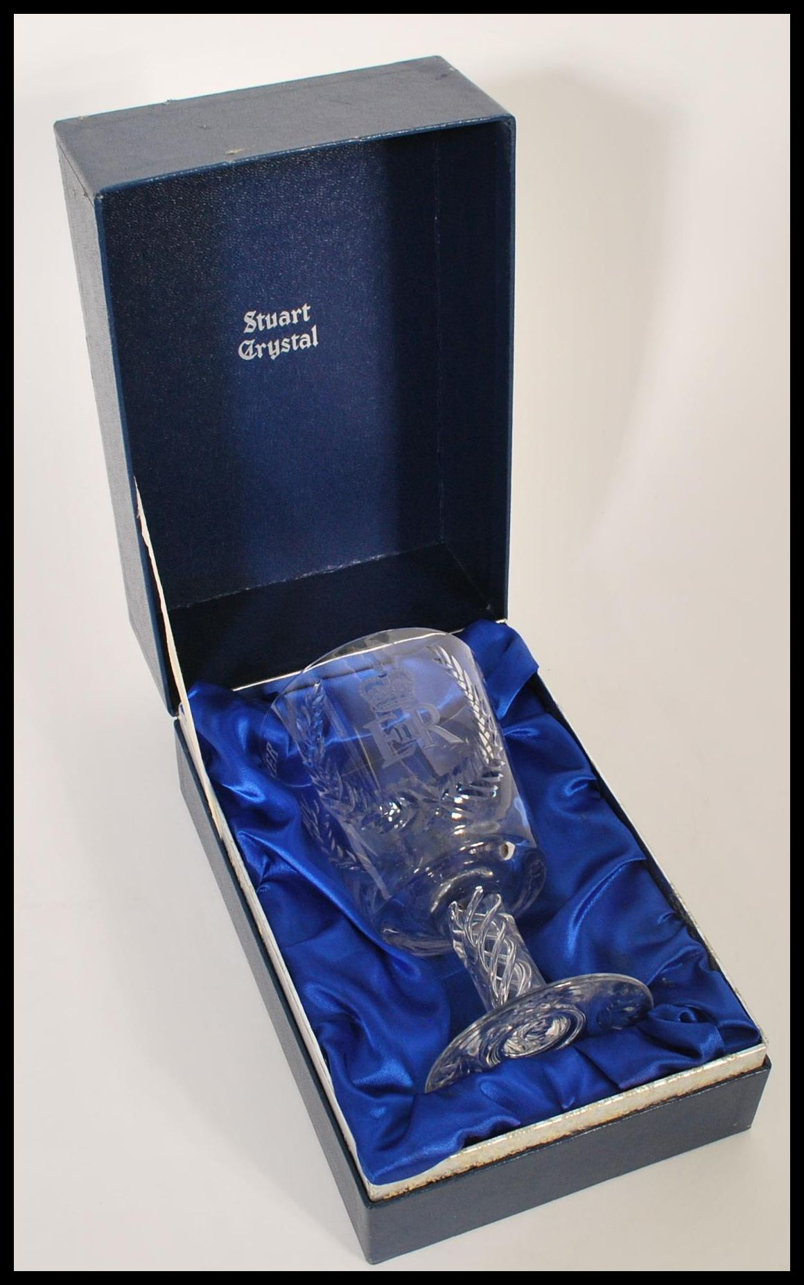 Lot 51 - A cased Stuart Crystal QE2 Silver Wedding cut glass large goblet raised on circular foot with air