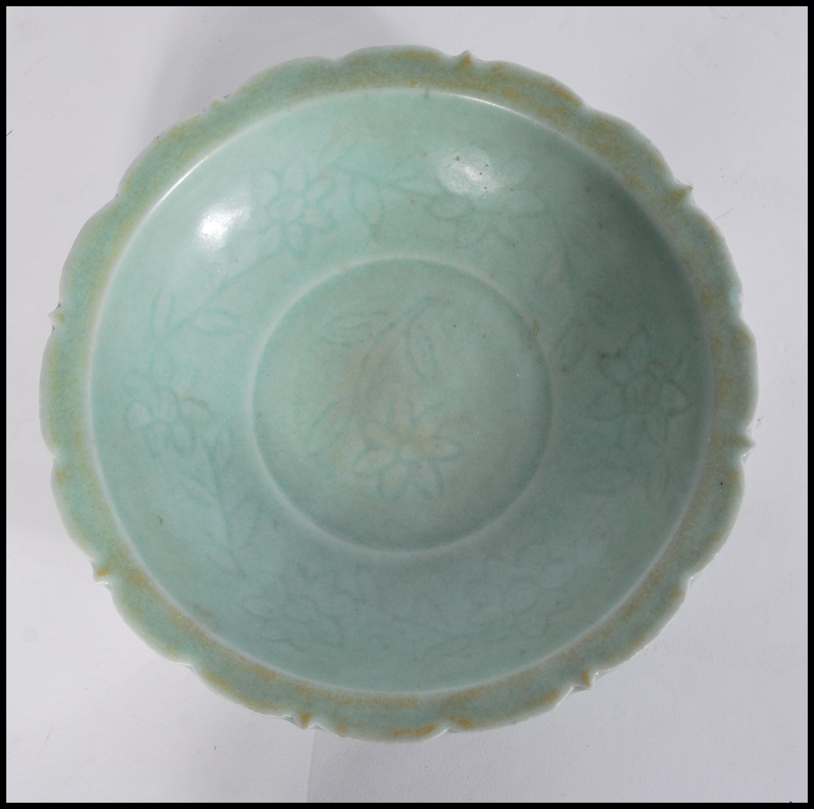 Lot 49 - A Chinese celadon glaze bowl of scalloped form having floral motifs and decoration.Measures 5cm-