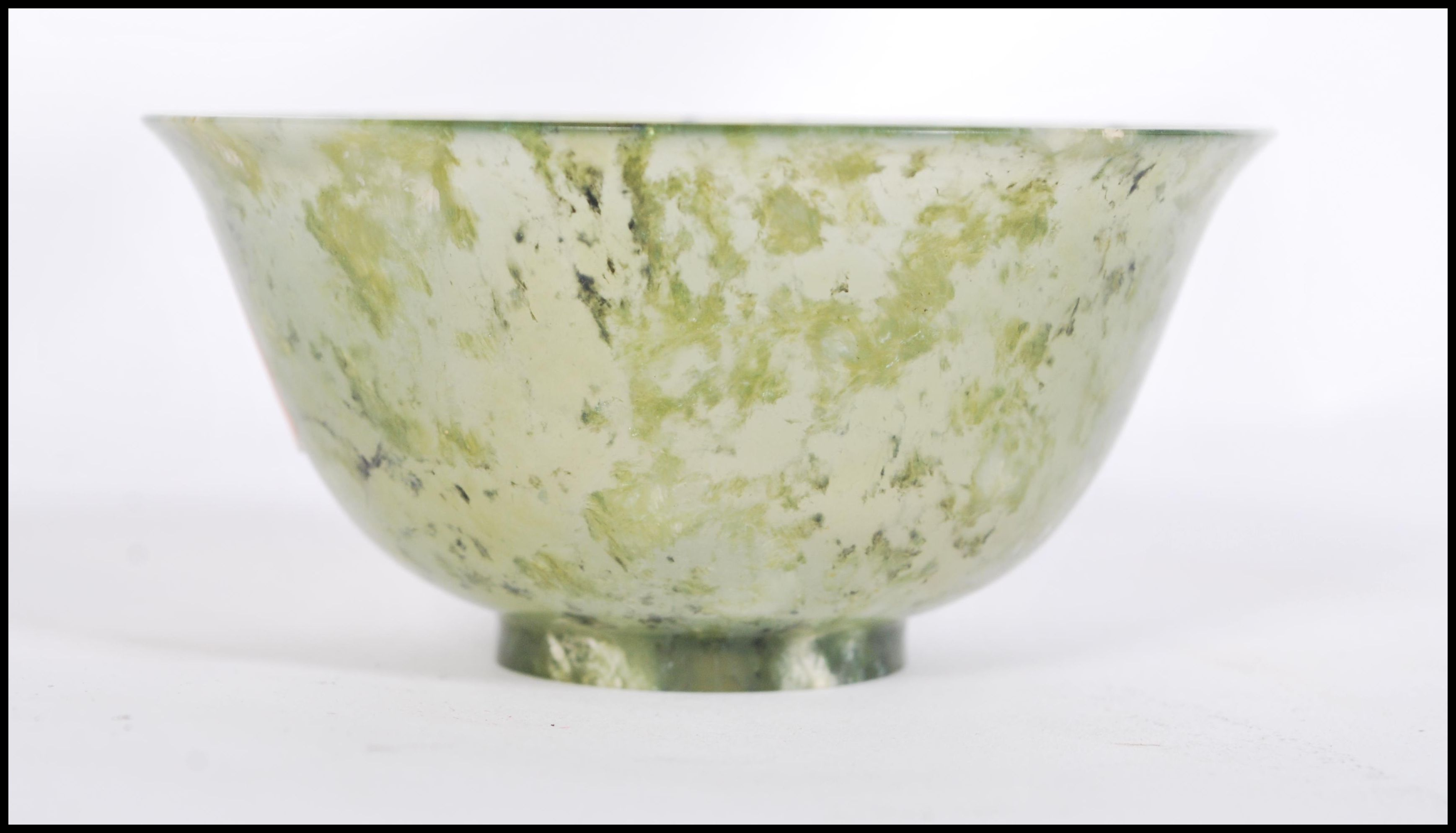 Lot 36 - A Chinese jade tea / finger bowl / libation cup of typical form having a mottled and clear