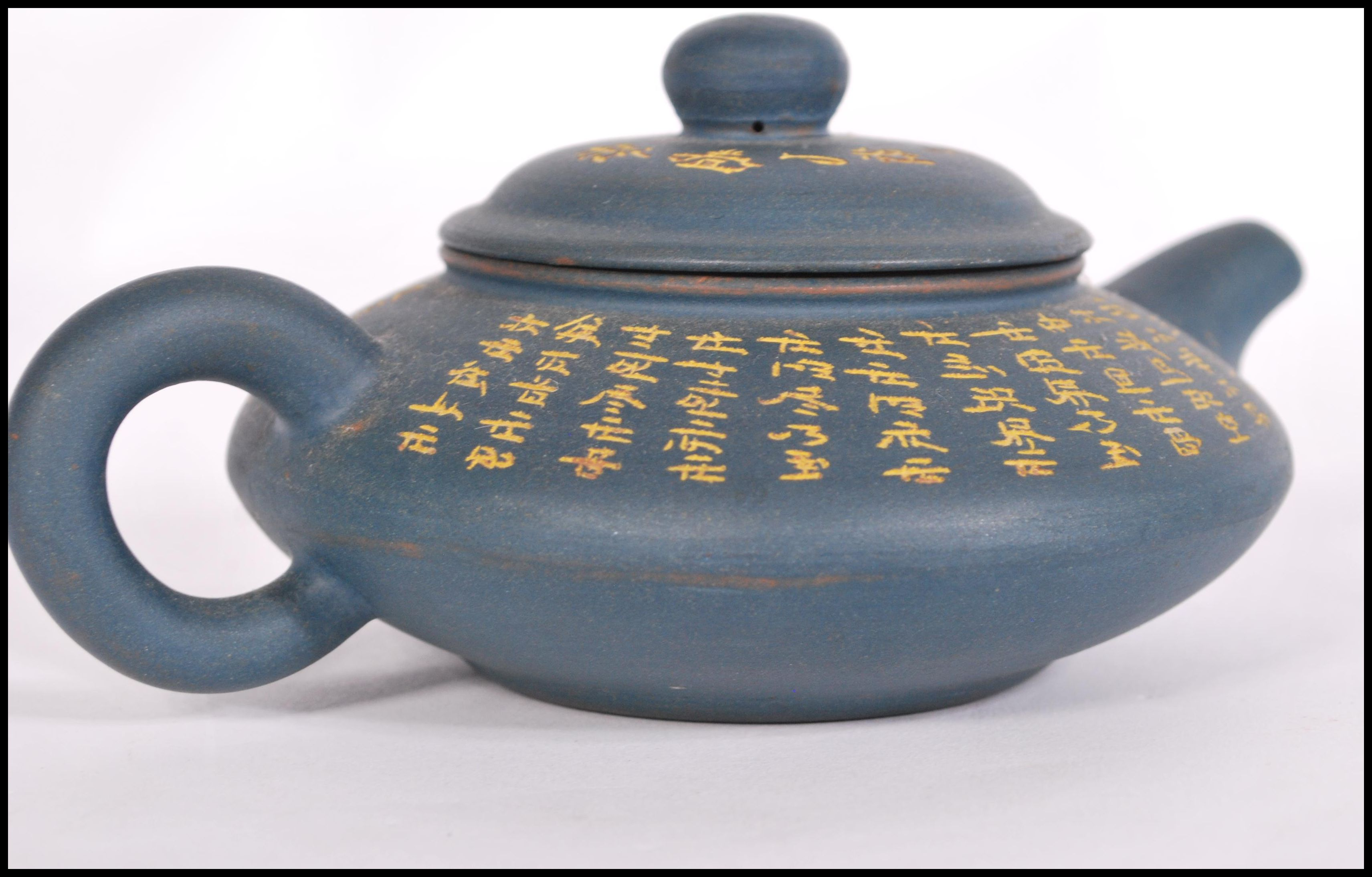 Lot 44 - A Chinese Yi Xing teapot having a blue pottery ground with gilt Buddhist Scriptures and