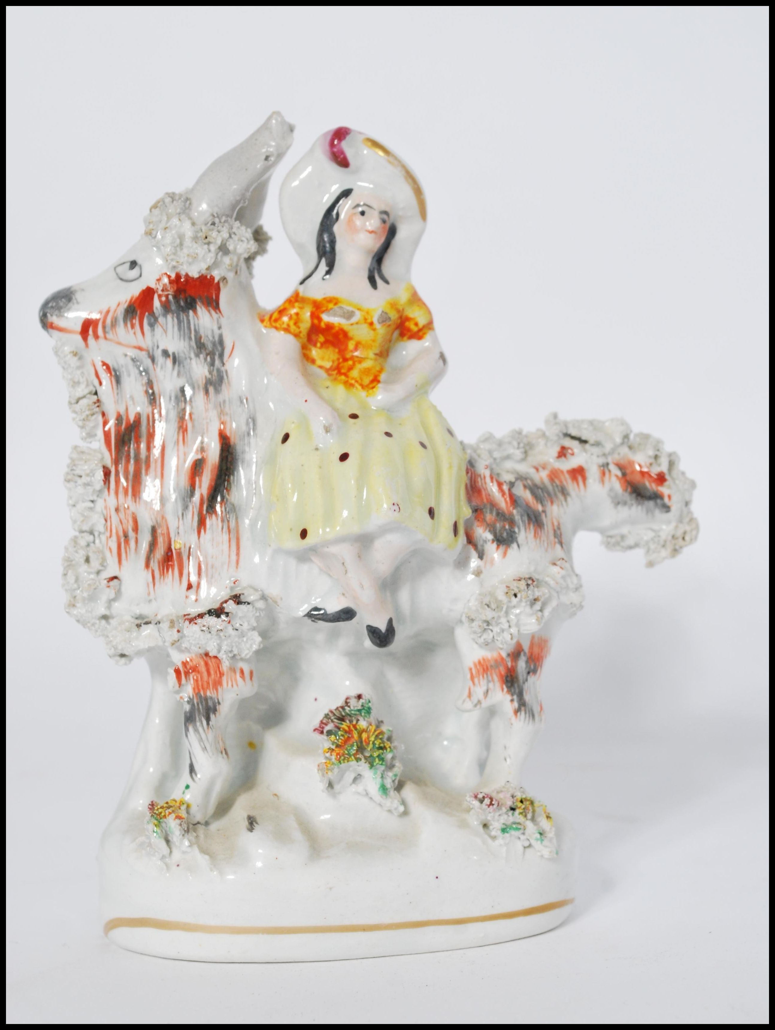 Lot 31 - A Victorian Staffordshire flat back ceramic figurine of a goat and lady. Together with another