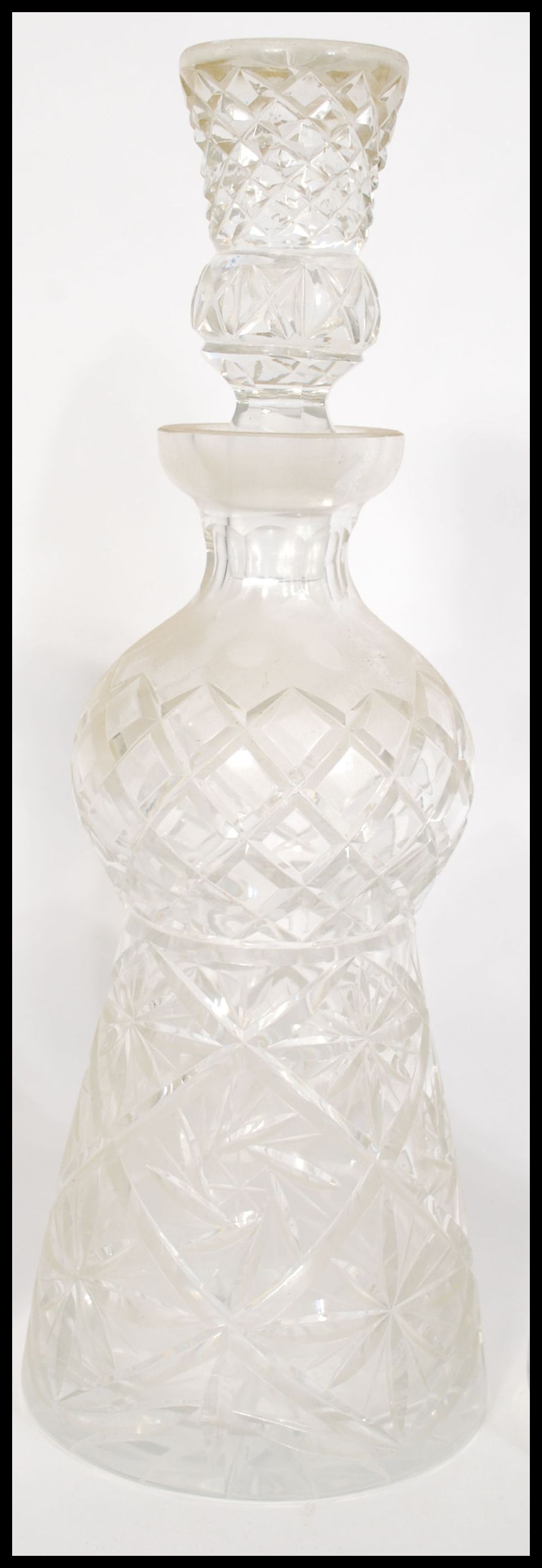 Lot 8 - A group of three vintage cut glass decanters to include a thistle shaped decanter with thistle