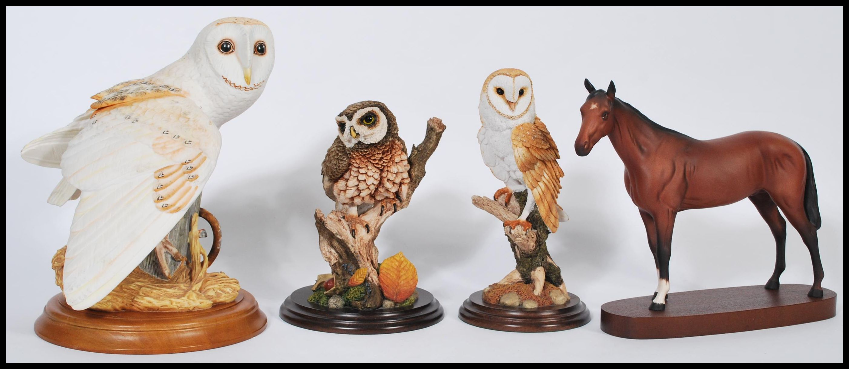 Lot 29 - A group of ceramic and resin animals to include a Royal Doulton ceramic horse on wooden base, a