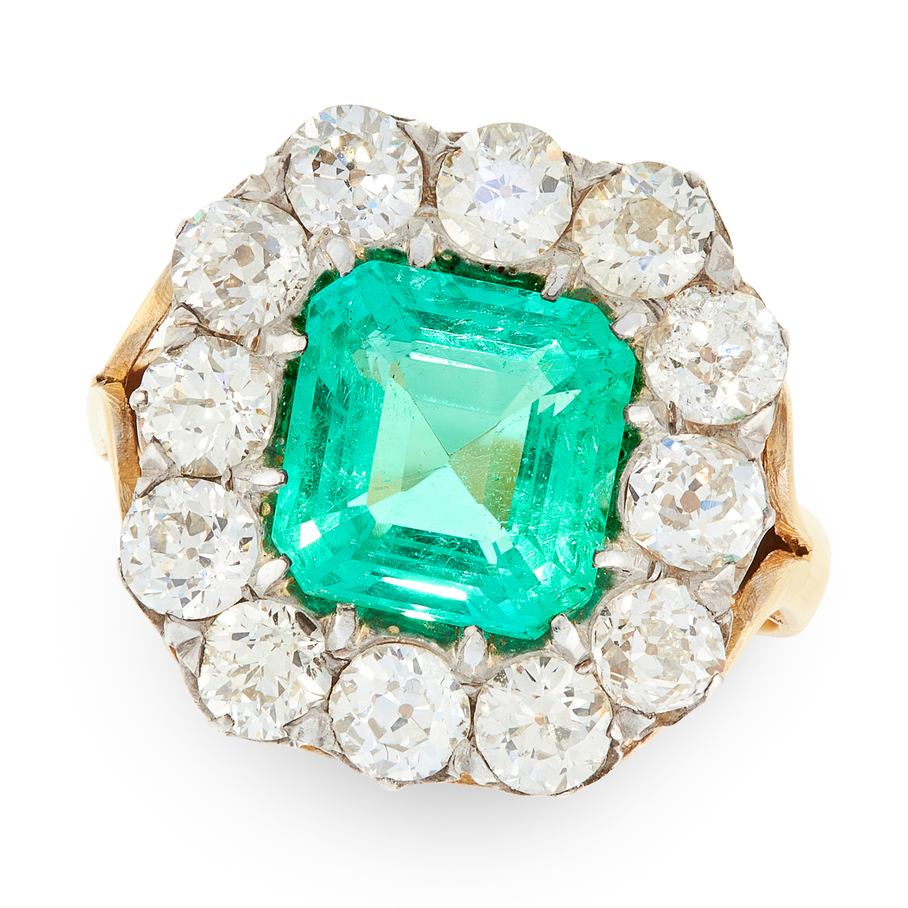 A COLOMBIAN EMERALD AND DIAMOND CLUSTER RING in 18ct yellow gold and silver, set with an emerald cut