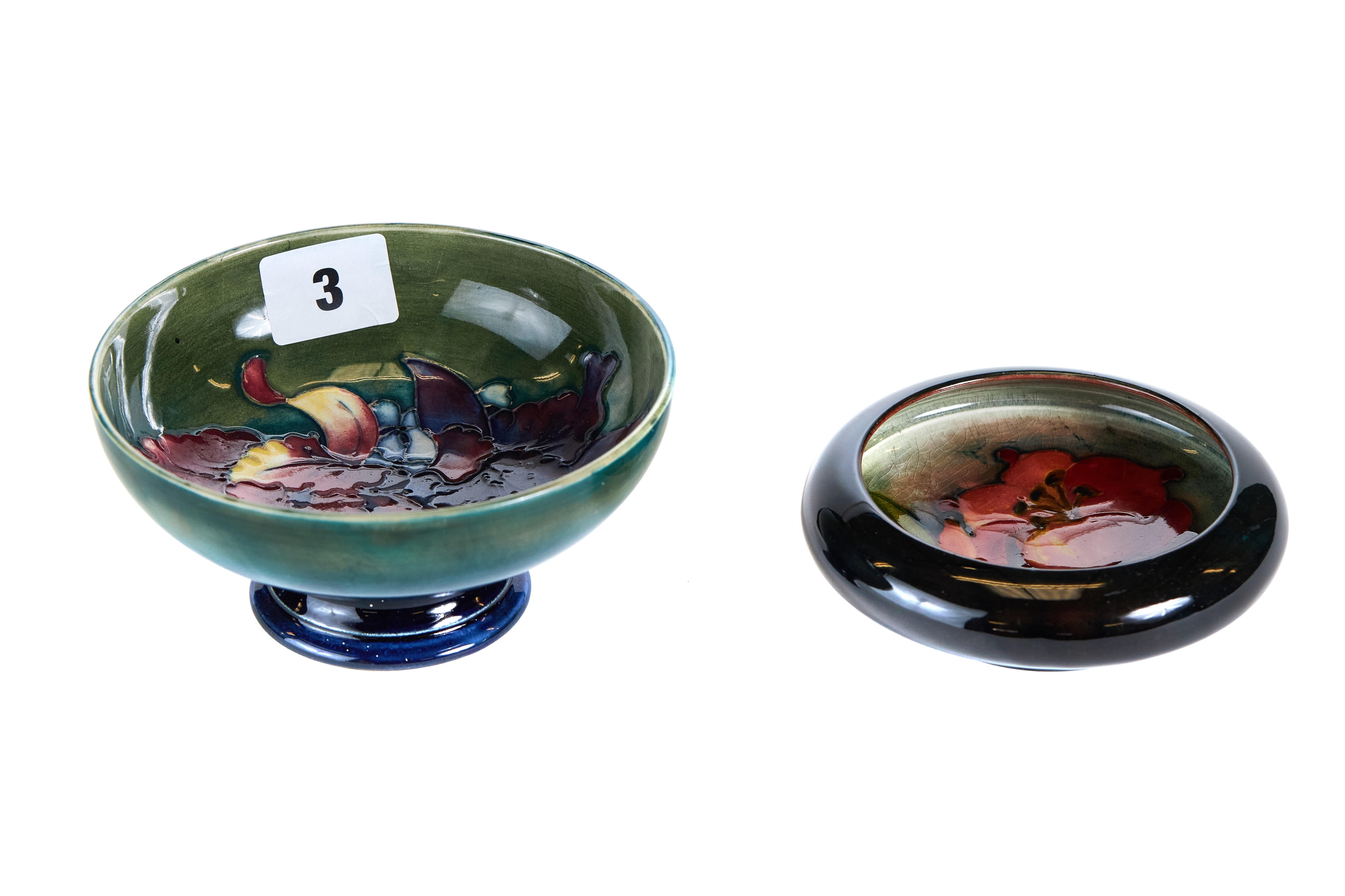 A 20TH CENTURY MOORCROFT POTTERY GREEN GLAZED PEDESTAL BOWL internally decorated with flowers,