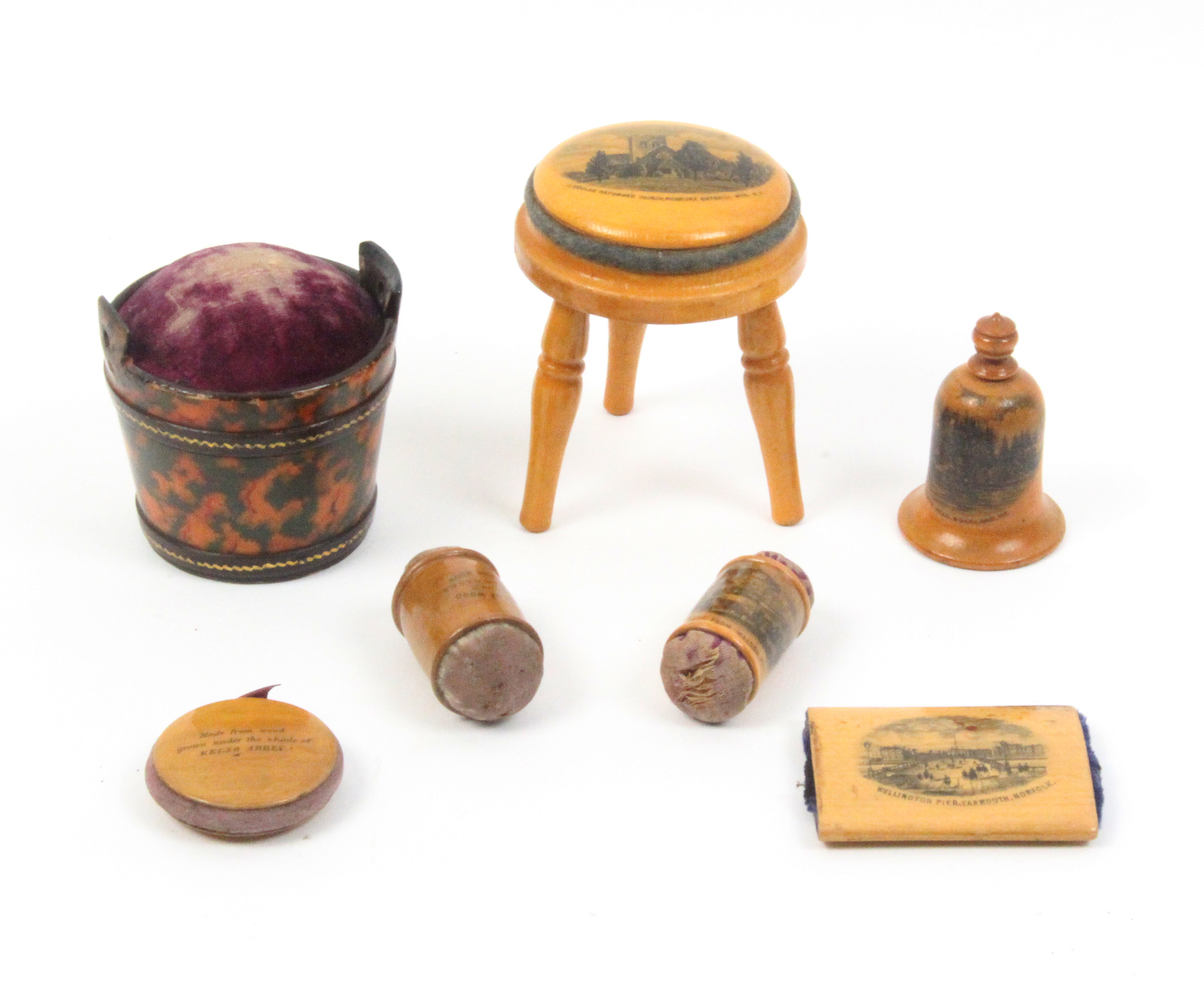 Mauchline ware - sewing - seven pieces comprising a pincushion in the form of a stool (J. Gould