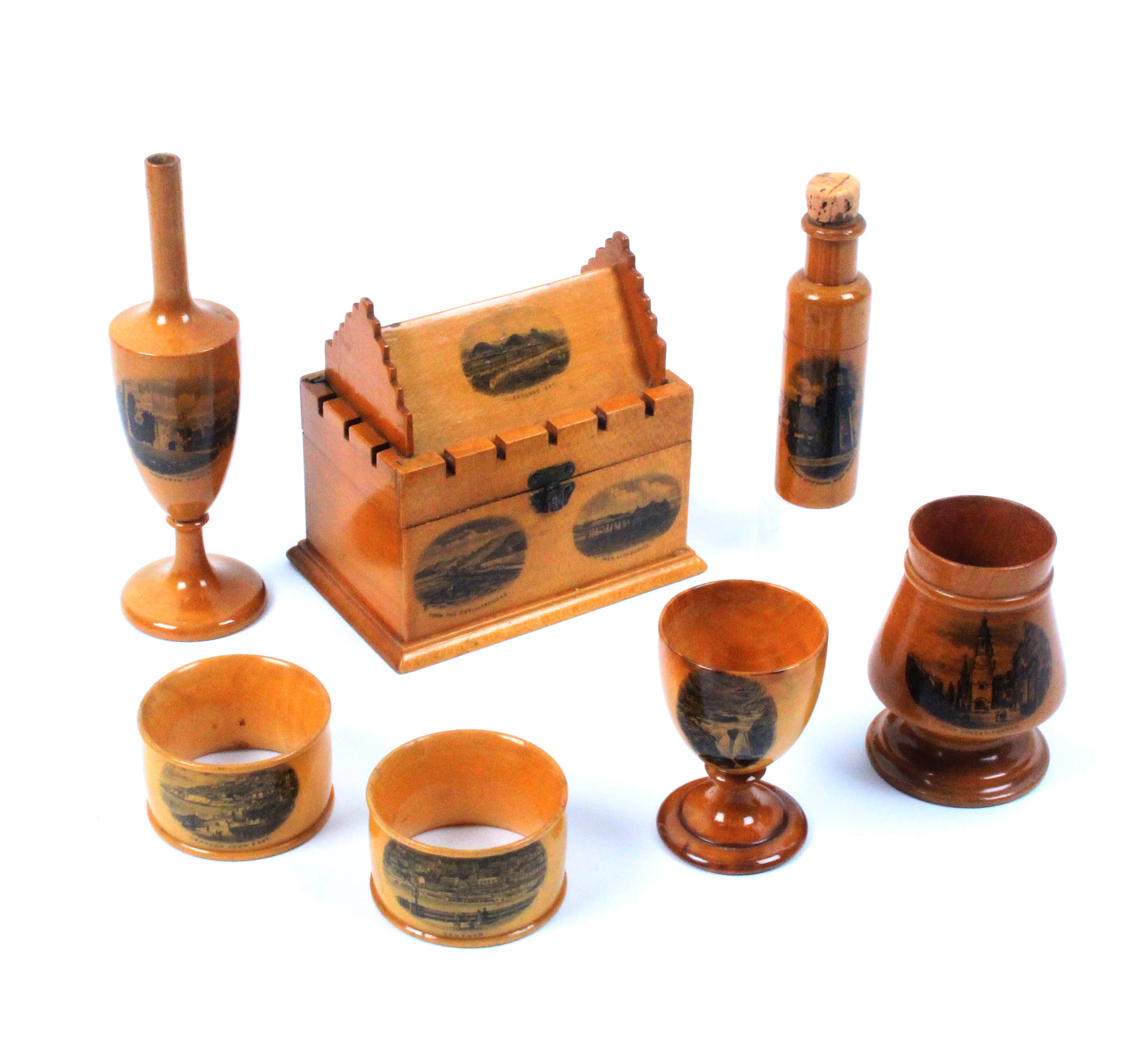 Mauchline ware - seven pieces - a crenalated rectangular box with pitched roof (Llandudno Bay/From