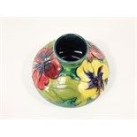 A Moorcroft vase of squat form with drawn neck and with raised and painted hibiscus decoration in
